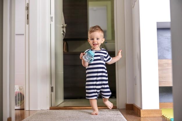 Aanbiddelijke glimlachende jongere die zijn fles met water houdt en zijn eerste stappen zet. Premium Foto