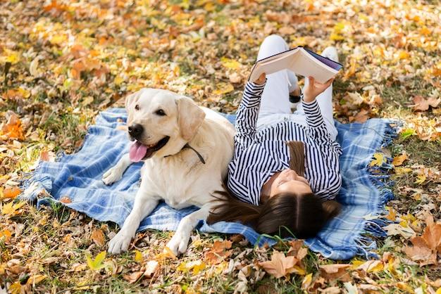 Aanbiddelijke hond met vrouw in het park Gratis Foto