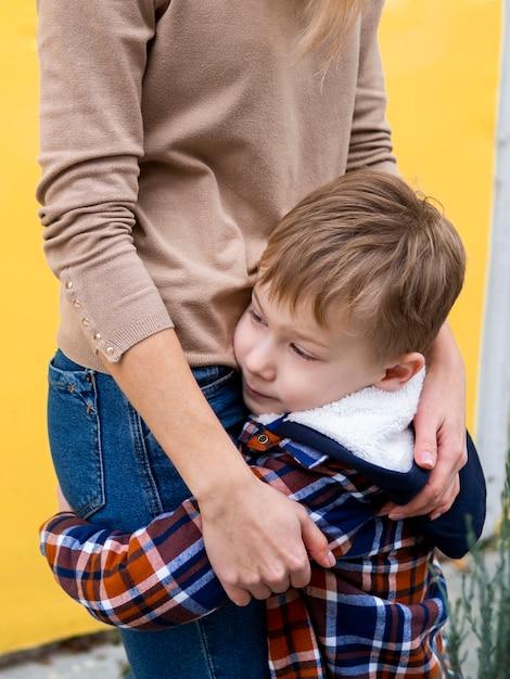 Aanbiddelijke jonge jongen die zijn moeder houdt Gratis Foto