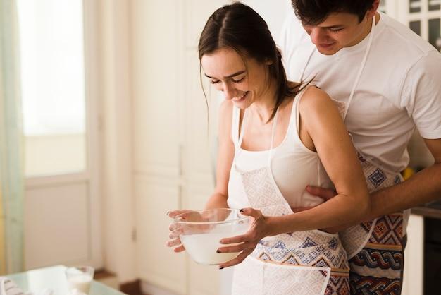 Aanbiddelijke jonge man en vrouw die samen koken Gratis Foto