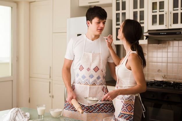 Aanbiddelijke jonge vrouw en man samen in de keuken Gratis Foto