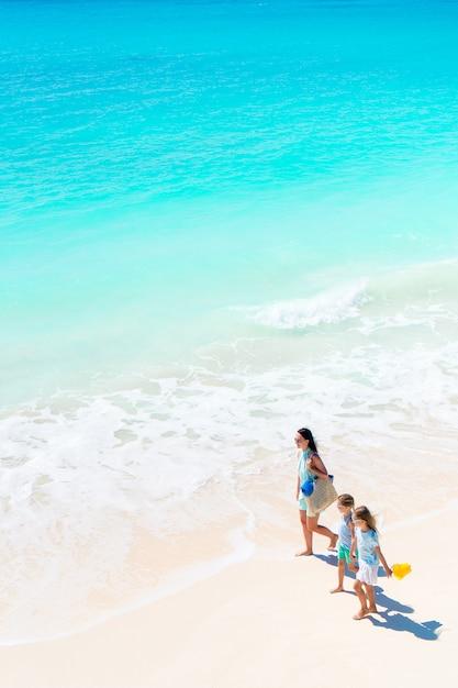 Aanbiddelijke kleine meisjes en jonge moeder op wit strand. uitzicht op de familie en de oceaan van bovenaf Premium Foto