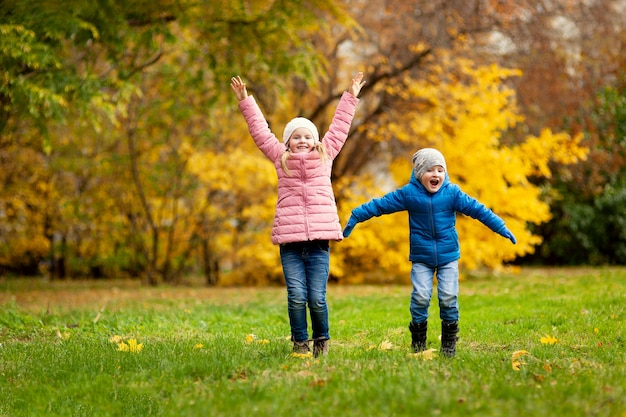 Aanbiddelijke meisje en jongen in openlucht bij mooie de herfstdag Premium Foto