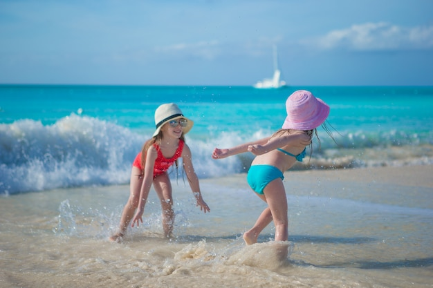 Aanbiddelijke meisjes die in ondiep water bij exotisch strand spelen Premium Foto