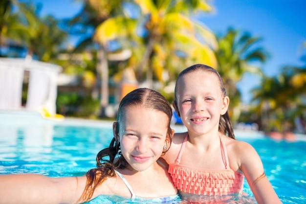 Aanbiddelijke meisjes die in openlucht zwembad spelen. leuke kinderen nemen selfie. Premium Foto