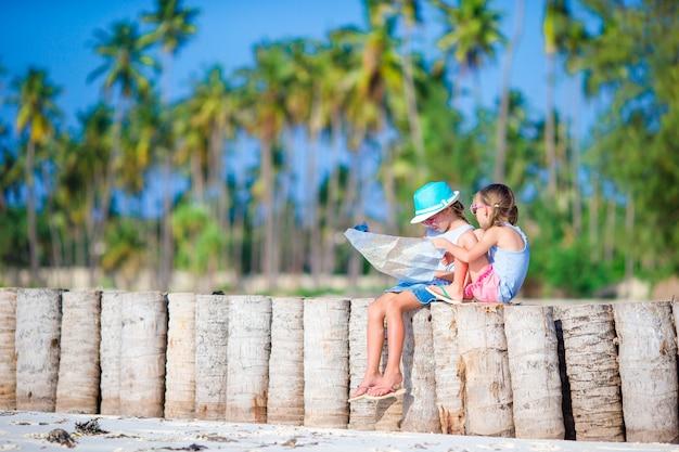 Aanbiddelijke meisjes met grote kaart van eiland op strand Premium Foto