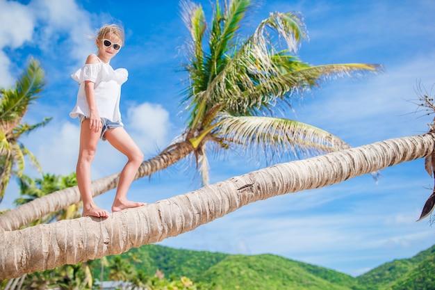 Aanbiddelijke meisjezitting op palm tijdens de zomervakantie op wit strand Premium Foto