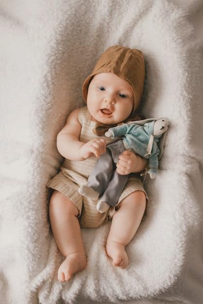 Aanbiddelijke mooie pasgeboren mannelijke baby met hierboven het glimlachen het gelukkige portret van de gezichtslevensstijl van. grappig zuigelingskind dat met stuk speelgoed in mand ligt die met witte sprei wordt behandeld. Premium Foto