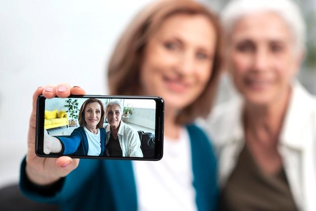 Aanbiddelijke rijpe vrouwen die een selfie nemen Gratis Foto