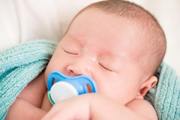 Aanbiddelijke slapende pasgeboren baby met fopspeen in de mond Premium Foto