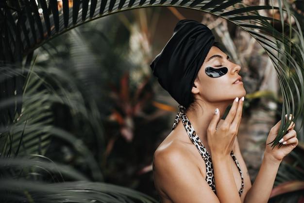 Aanbiddelijke vrouw in zwarte tulband die zich op aardachtergrond bevindt. buiten schot van elegante dame met ooglapjes in de buurt van palmbomen. Gratis Foto