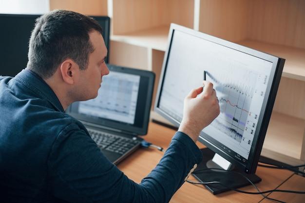 Aandacht vestigen op elk moment. polygraaf-examinator werkt op kantoor met de apparatuur van zijn leugendetector Gratis Foto