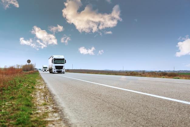 Aangekomen witte vrachtwagen op de weg in een landelijk landschap bij zonsondergang Premium Foto