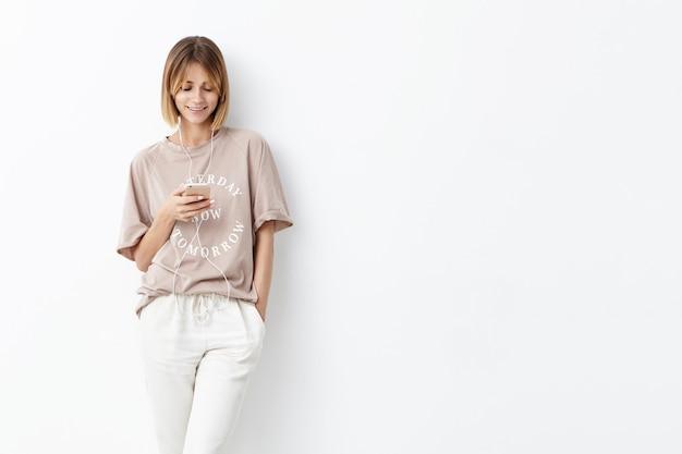 Aangenaam ogende vrouw met trendy kapsel, hand in zak houden, mobiele telefoon gebruiken voor communicatie met vrienden of geliefde, luisteren naar aangename muziek, goed humeur hebben in de vroege ochtend Gratis Foto