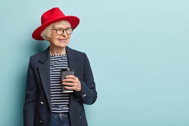 Aangenaam uitziende blije volwassen vrouw drukt positieve emoties uit, draagt een elegant jasje en een rode hoed, houdt een wegwerpbeker vast, drinkt warme drank, gefocust opzij, glimlacht breed Gratis Foto