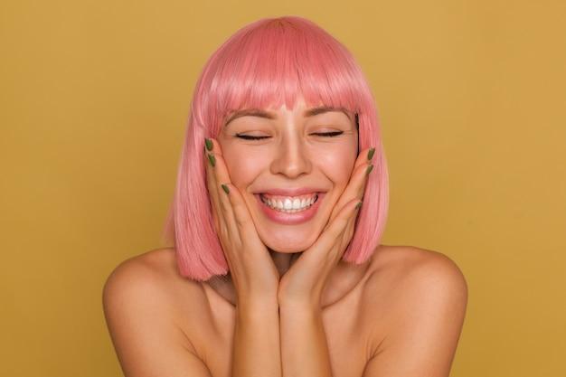 Aangenaam uitziende gelukkige jonge dame met kort roze haar die haar gezicht vasthoudt met opgeheven handpalmen terwijl ze poseert over de mosterdmuur, de ogen gesloten houdt terwijl ze breed lacht Gratis Foto