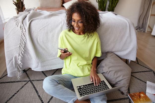 Aangenaam uitziende jonge donkerharige vrouw met krullen werken op de vloer van de slaapkamer, smartphone in de hand houden en laptop op benen houden, goed nieuws ontvangen, vreugdevol glimlachen Gratis Foto