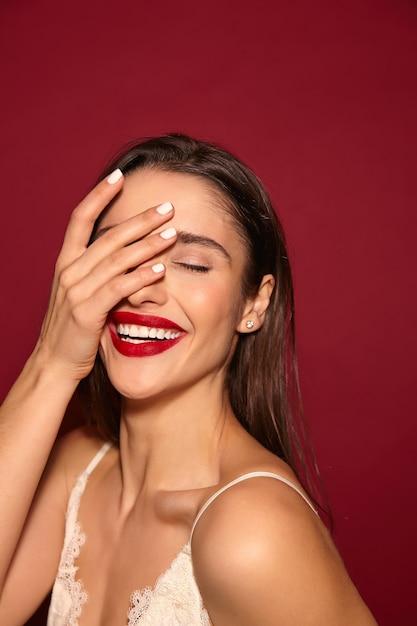 Aangenaam uitziende jonge mooie blije langharige brunette dame met rode lippen Gratis Foto