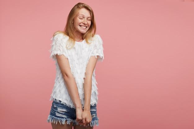 Aangenaam uitziende jonge vrolijke roodharige dame gekleed in wit feestelijk t-shirt en spijkerbroek korte broek handen naar beneden houden terwijl poseren op roze achtergrond, gelukkig lachend met gesloten ogen Gratis Foto