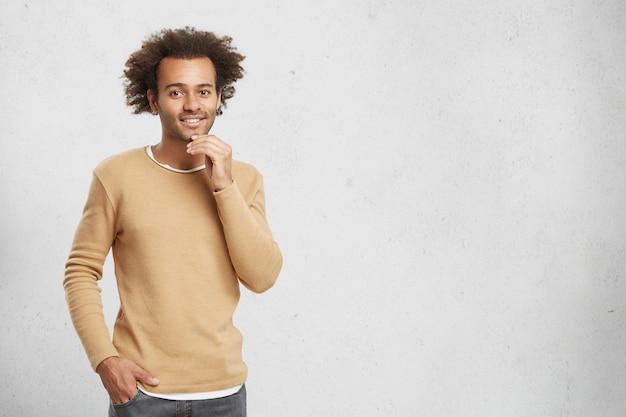 Aangenaam uitziende man van gemengd ras met trendy kapsel, nonchalant gekleed, houdt de hand op de kin Gratis Foto