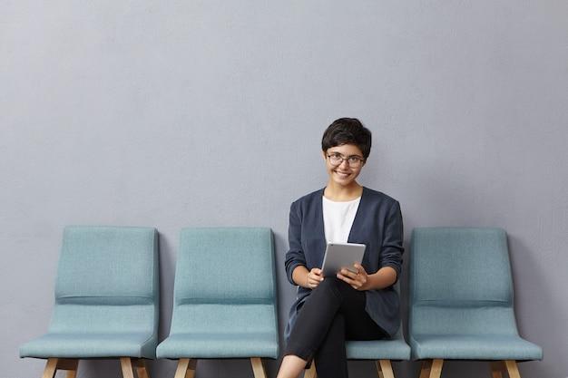 Aangenaam uitziende vrouw van gemengd ras heeft een kort trendy kapsel, draagt een bril en een formeel jasje, komt naar een sollicitatiegesprek, Gratis Foto