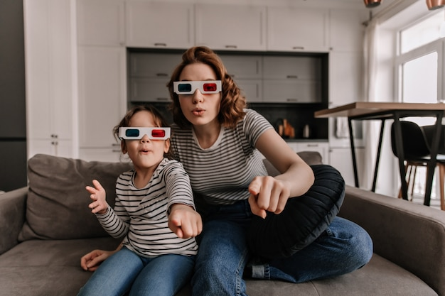 Aangenaam verrast moeder en dochter zitten in 3d-bril op de bank en kijken naar film. Gratis Foto
