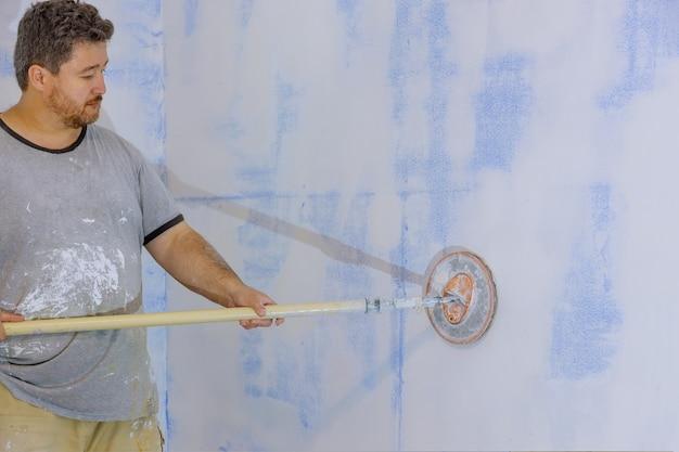 Aannemer die zandtroffel gebruikt die de gipsplaat op de muur schuurt Premium Foto