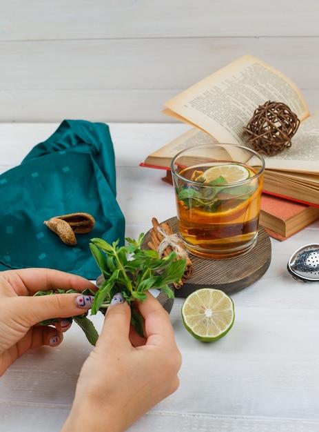 Aantal boeken, citroen, munt en groene sjaal en kruidenthee en kaneel op een houten bord Gratis Foto