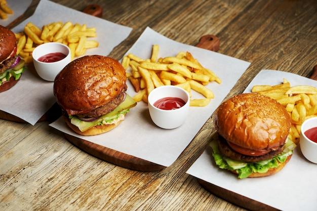 Aantal hamburgers met frietjes en ketchupsaus. grote hamburgers en frietjes op houten tafel achtergrond. fastfood achtergrond instellen. restaurant hamburgermenu Premium Foto
