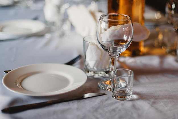 Aantal lege glazen en borden met bestek op een wit tafellaken op de tafel in het restaurant Premium Foto