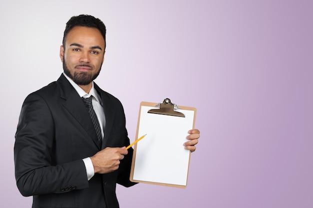 Aantekeningen maken. vrolijke jonge afrikaanse zakenman die iets in zijn blocnote schrijft Premium Foto