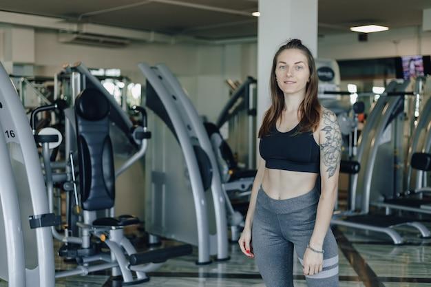 Aantrekkelijk atletisch meisje staat op de muur van simulatoren in de sportschool. gezonde levensstijl. Gratis Foto