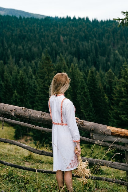 Aantrekkelijk blond meisje in witte jurk met borduurwerk poseren met aartjes boeket in de buurt van houten hek over schilderachtig landschap Premium Foto