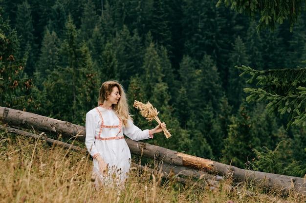 Aantrekkelijk blond meisje in witte jurk met borduurwerk poseren met aartjes boeket over schilderachtig landschap Premium Foto