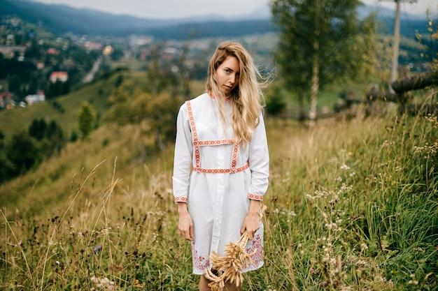 Aantrekkelijk blond meisje in witte jurk met ornament poseren met aartjes boeket over schilderachtig landschap van het platteland Premium Foto