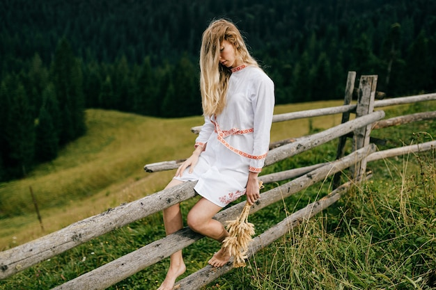 Aantrekkelijk blond meisje in witte jurk met ornament zittend op een houten hek met aartjes boeket over schilderachtig landschap van het platteland Premium Foto