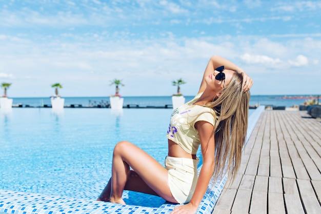 Aantrekkelijk blond meisje met lang haar zit in de buurt van zwembad. ze poseert en kijkt naar boven. Gratis Foto
