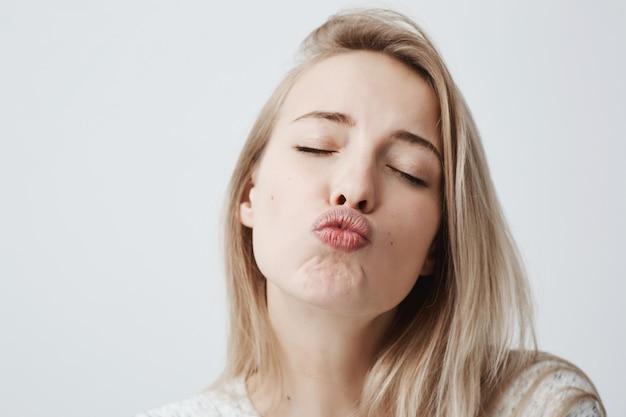 Aantrekkelijk dromerig vrouwelijk model met blond haar sluit ogen, pruilt lippen, stuurt kusjes Gratis Foto