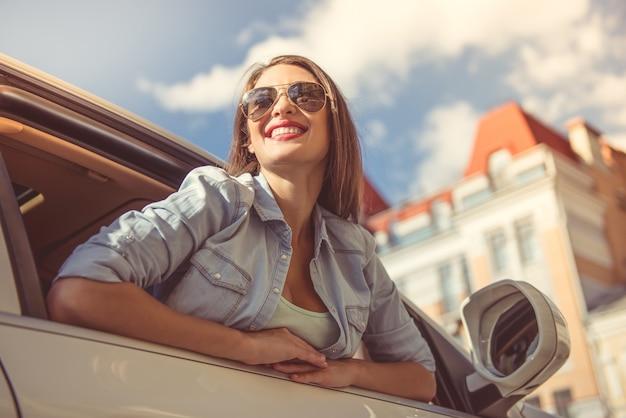 Aantrekkelijk gelukkig meisje in stijlvolle kleding en zonnebril. Premium Foto