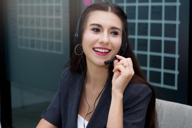Aantrekkelijk glimlachend kaukasisch vrouwencall centre met microfoonhoofdtelefoon die klant aanbieden Premium Foto
