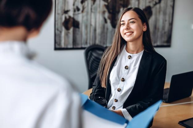 Aantrekkelijk, glimlachend meisje werkt op kantoor met haar collega. Premium Foto