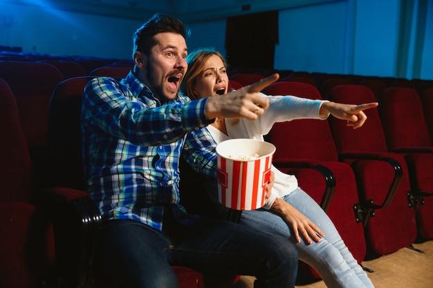 Aantrekkelijk jong kaukasisch paar dat een film bekijkt in een bioscoop, een huis of een bioscoop. zie er expressief, verbaasd en emotioneel uit. alleen zitten en plezier maken. relatie, liefde, familie, weekendtijd. Gratis Foto