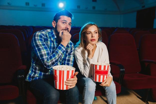 Aantrekkelijk jong koppel kijken naar een film in een bioscoop Gratis Foto