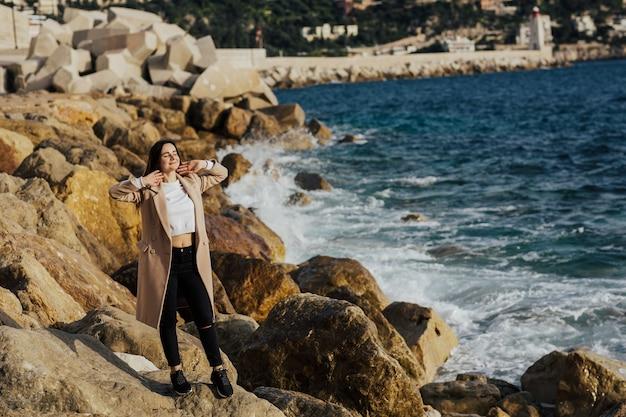 Aantrekkelijk jong meisje poseren op rotsachtig strand. Premium Foto