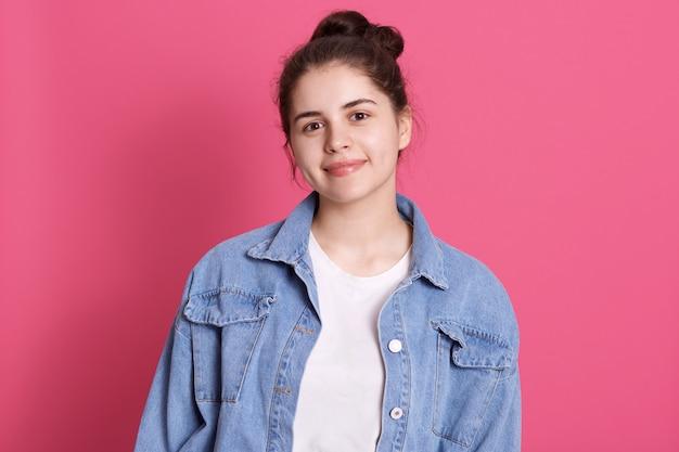 Aantrekkelijk kaukasisch tienermeisje kleedt casual spijkerjasje en wit overhemd, heeft haarknotje Gratis Foto
