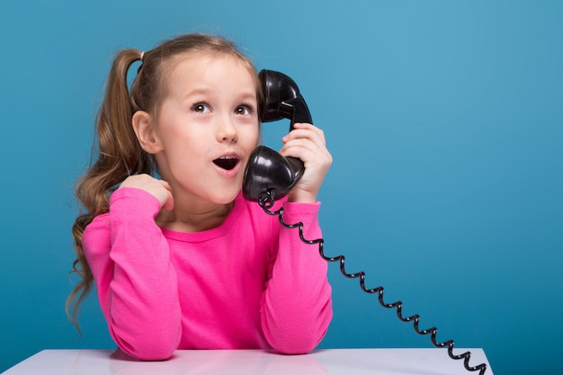 Aantrekkelijk klein schattig meisje in roze shirt met aap en blauwe broek houden lege poster en praat een telefoon Premium Foto
