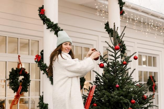 Aantrekkelijk lachend meisje siert een kerstboom in de buurt van het huis Premium Foto
