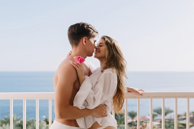 Aantrekkelijk langharig meisje met roze bloem in hand zachtjes aanraken van jonge brunette man en op zoek in zijn ogen. man met trendy kapsel omhelst zijn charmante vriendin en kuste haar Gratis Foto