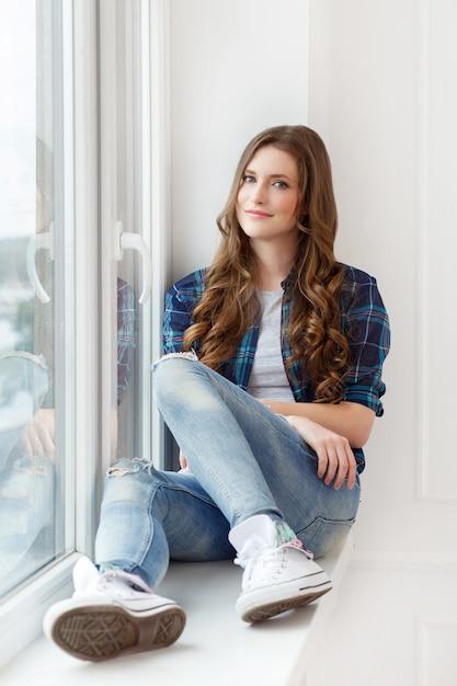 Aantrekkelijk meisje bij het raam Gratis Foto