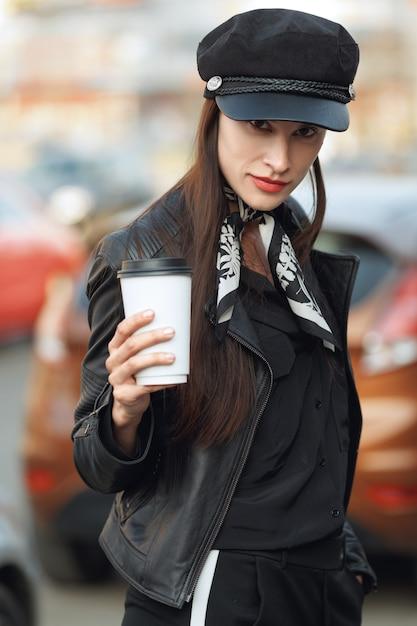 Aantrekkelijk meisje dat langs de straat met kop van koffie loopt Premium Foto